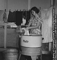 Photo of woman washing clothes in old-fashioned washing machine.