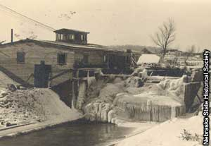 Photo of a waterwheel frozen over with ice.